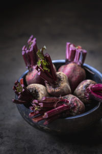 bowl of red beets in a blue bowl with a dark background