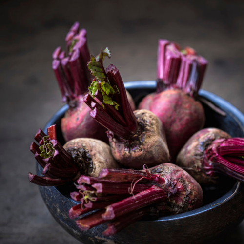 purple beets in a black bowl with dark brown background