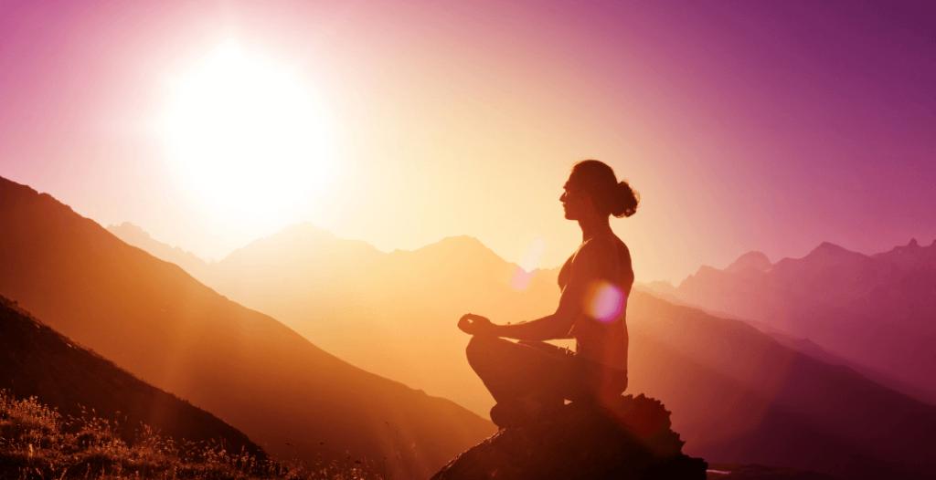 Woman meditating on hilltop at sunrise