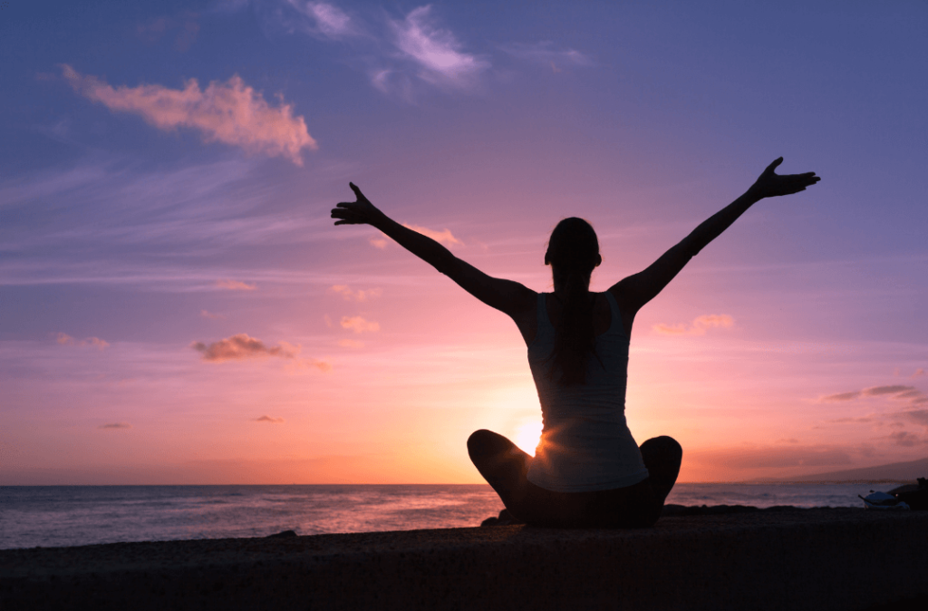 Woman with arms stretched up at sunrise