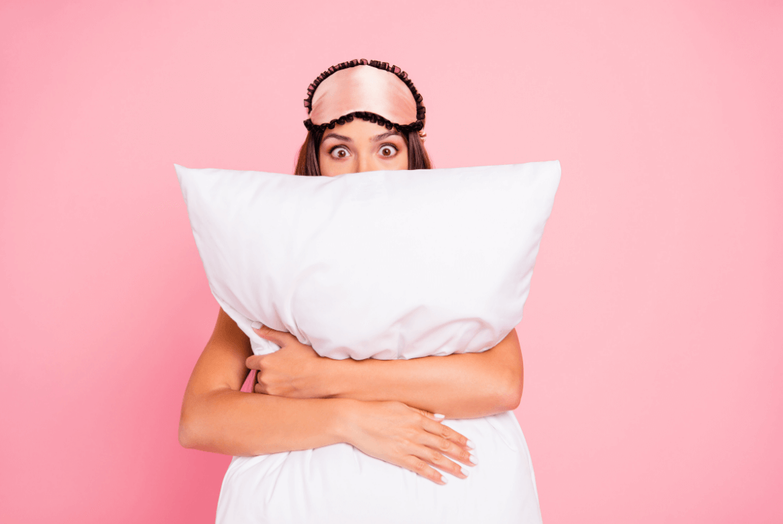 Woman holding pillow and wearing eye mask looking awake