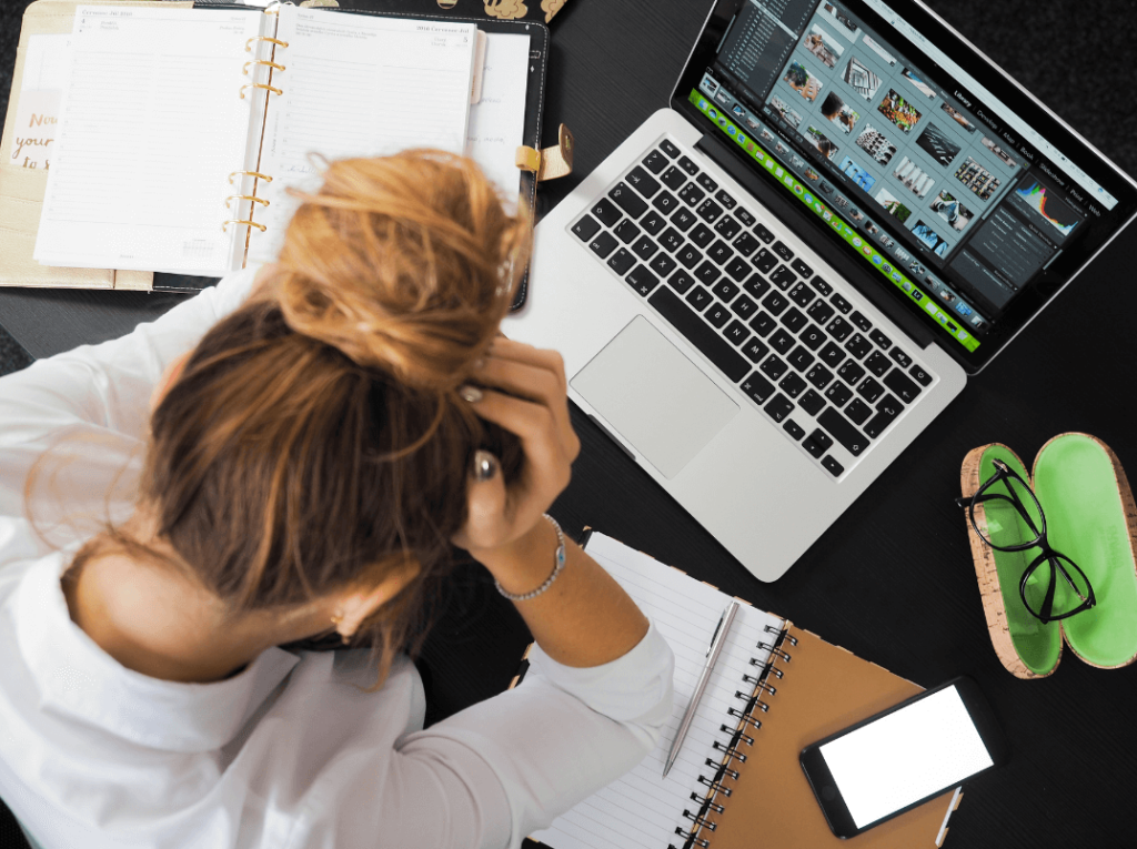 stressed out woman with head in her hands at a desk with a laptop, phone, and 2 journals