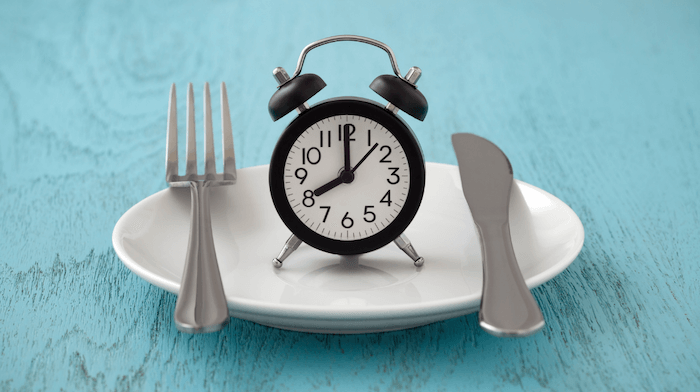fork knife and black alarm clock on white plate on blue wood surface