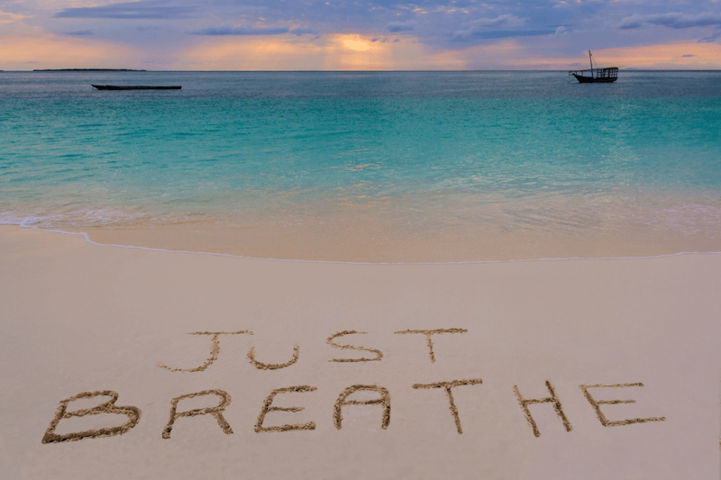 the words just breathe scratched into the sand on the beach at sunset