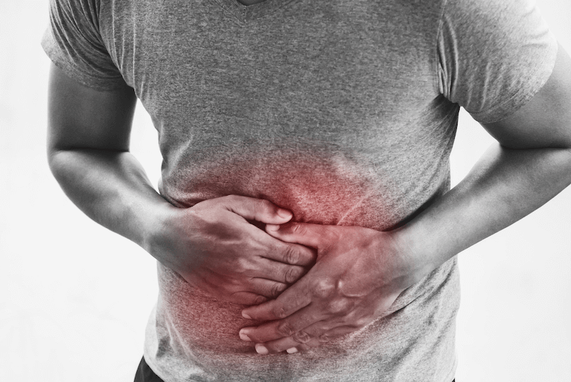 man in black and white grabbing stomach highlighted in red