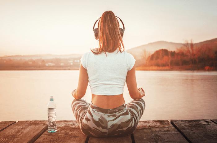 woman in camo yoga pants sitting on dock meditating with headphones