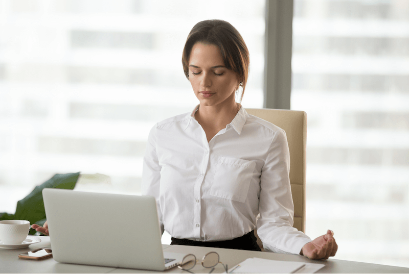woman meditating at her desk in front of her laptop
