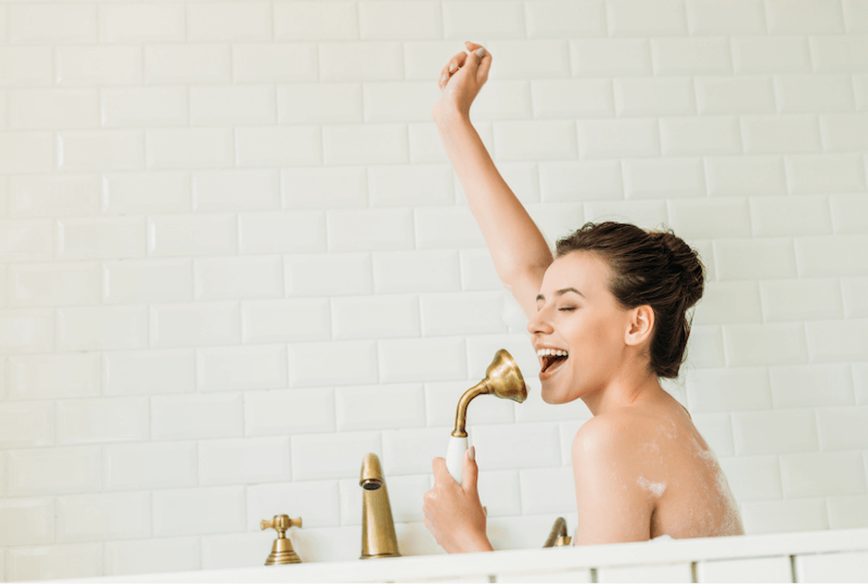 woman singing into her shower head in the bathtub