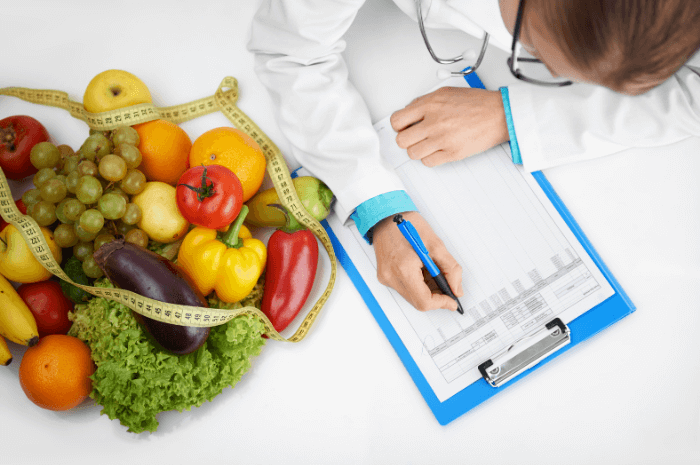dietitian woman in white lab coat writing on clipboard with colorful fruits and vegetables and yellow measuring tape on white background
