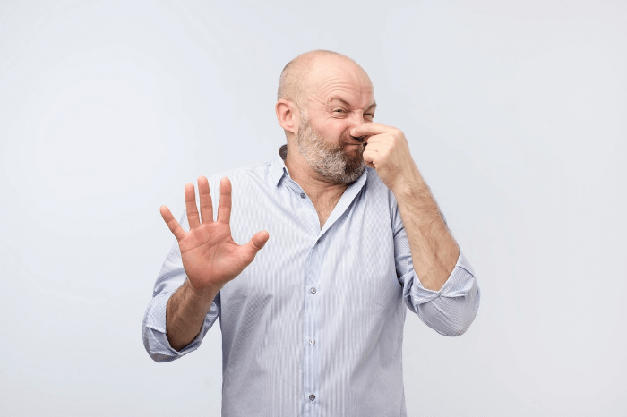 man holding nose and holding hand up something is stinky on white background
