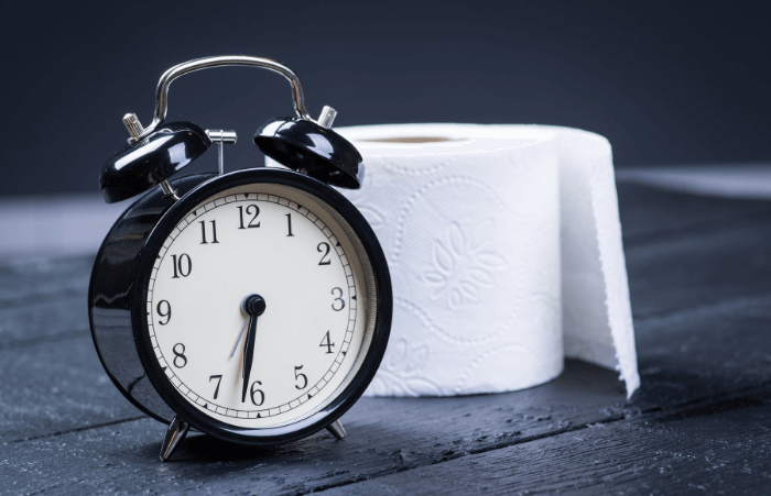 toilet paper roll with black alarm clock with dark background