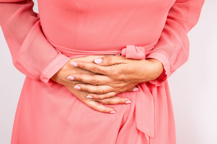 woman in pink long sleeve dress holding stomach on white background