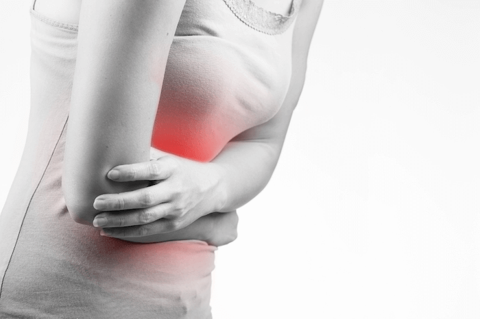 woman in black in white holding stomach in pain glowing red