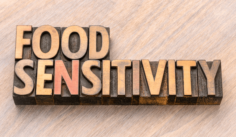 """wooden block letters spelling out the words """"food sensitivity"""" on a light colored wood background"""