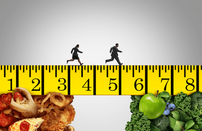 man and woman running across a measuring tape away from fried foods and pizza to greens fruits and vegetables