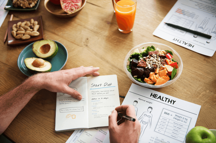 man writing in food journal with healthy foods on the table in front of him