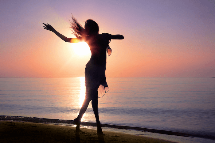 woman in silhouette dancing on the beach with a pink and purple sunset